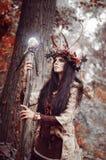 Mooi brunette met geschilderd gezicht, klerenmedicijnman, een bloemenkroon op haar hoofd en hoornen, die een gloeiend houten pers Royalty-vrije Stock Fotografie