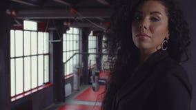 Mooi brunette met krullend haar en een zwarte kleding in de gymnastiek stock videobeelden