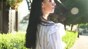 Mooi brunette met lang haar die dichtbij shop-windows in centrum van stad lopen stock video