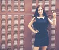 Mooi brunette met lang haar in een korte zwarte die twee vingers tonen dichtbij metaal bruine omheining Kleurrijke hipsterfoto Royalty-vrije Stock Afbeelding
