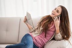 Mooi brunette op de krant van de telefoonholding Royalty-vrije Stock Fotografie