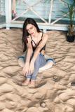 Mooi brunette op het strand in jeans en het zwempak Stock Afbeelding
