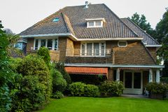 Mooi buitenhuis met groen gazon en aanplantingen in werf Villa Plattelandshuisje met gazon Royalty-vrije Stock Afbeelding