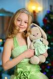 Mooi charmerend vrij blond kind-meisje op de achtergrond van een Nieuwjaarboom Stock Foto's