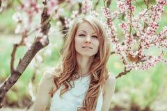 Mooi de lente blond meisje in bloeiende boom Stock Afbeelding