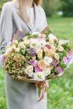 Mooi de lenteboeket in handen gevoelig bloemstuk met roze en groene kleurenbloemen gazon op achtergrond royalty-vrije stock afbeeldingen