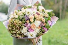 Mooi de lenteboeket in handen gevoelig bloemstuk met roze en groene kleurenbloemen gazon op achtergrond royalty-vrije stock afbeelding