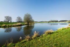 Mooi de lenteplatteland met de vijver royalty-vrije stock afbeelding