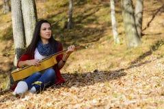 Mooi de spelermeisje van de vrouwengitaar in het bos Royalty-vrije Stock Afbeelding