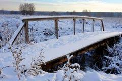 Mooi de winterlandscape Kleine houten voetbrug onder de sneeuw Stock Foto's