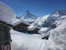 Mooi de winterlandschap met sneeuw behandelde plattelandshuisjes voor Matterhorn-berg stock afbeelding