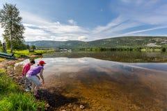 Mooi de zomerlandschap van een bergmeer met boten Een jonge jongen en een vrouw in de voorgrond royalty-vrije stock fotografie