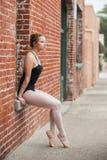 Mooi die balletmeisje op vensterzetel wordt gesteld stock afbeelding