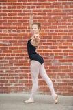 Mooi die balletmeisje voor rode bakstenen muur wordt gesteld stock fotografie
