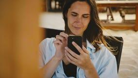 Mooi die close-up van gelukkige jonge onderneemster wordt geschoten die smartphonevermaak app gebruiken die op zitkamerligstoel g stock videobeelden