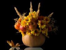 Mooi die de herfstboeket in pompoen, van bloemen en appelen wordt gemaakt, op zwarte worden geïsoleerd royalty-vrije stock afbeeldingen
