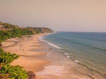 Mooi die en het ontspannen strand door groene palmen bij zonsondergang wordt geflankeerd Varkala, Kerala, India royalty-vrije stock fotografie