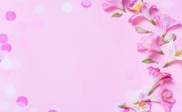 Mooi die kader van roze bloemen en roze confettien op roze achtergrond wordt gemaakt stock fotografie