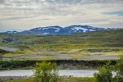 Mooi die landschap van heuvel met gras wordt behandeld en berg gedeeltelijk met sneeuw van stad van Alta, Noorwegen wordt behande royalty-vrije stock foto