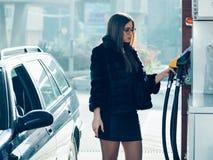 Mooi die meisje brandstof wordt gegoten in de tankauto's royalty-vrije stock foto's