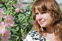 Mooi die meisje door kleurrijke bloemenmalve wordt omringd Stock Afbeelding