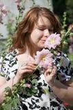 Mooi die meisje door kleurrijke bloemenmalve wordt omringd Stock Afbeeldingen