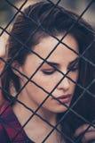 Mooi die vrouwenportret achter omheining in de stad wordt geschoten Stock Fotografie