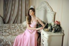 Mooi donker-haired meisje in de roze avondjurk Royalty-vrije Stock Afbeelding