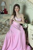 Mooi donker-haired meisje in de roze avondjurk Stock Afbeelding