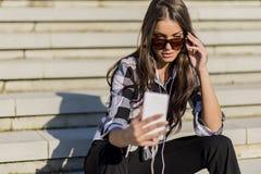 Mooi donkerbruin Kaukasisch meisje dat aan muziek luistert Stock Foto's