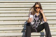 Mooi donkerbruin Kaukasisch meisje die aan de muziek met hij luisteren Royalty-vrije Stock Afbeelding