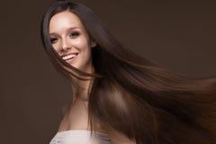 Mooi donkerbruin meisje in beweging met een volkomen vlot haar, en klassieke samenstelling Het Gezicht van de schoonheid stock afbeelding