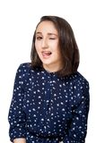 Mooi donkerbruin meisje in blauwe blouse die rond het hebben van pret voor de gek houden die tong tonen die met een grijns de cam stock fotografie