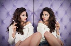 Mooi donkerbruin meisje in denimborrels en het witte blouse stellen op lilac geweven achtergrond die en een spiegel roken onderzo Stock Foto