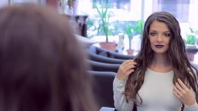 Mooi donkerbruin meisje die en haar kapsel in een spiegel glimlachen bekijken stock video