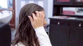 Mooi donkerbruin meisje die en haar kapsel in een spiegel glimlachen bekijken stock footage
