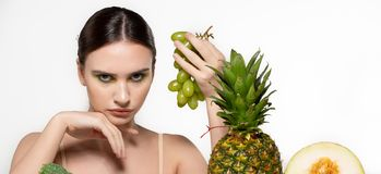 Mooi donkerbruin meisje die met heldere make-up groene druiven in hand houden, bekijkend camera, vruchten en groenten op stock afbeeldingen