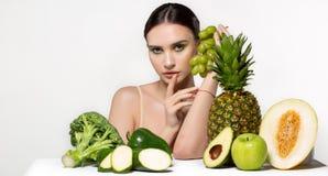 Mooi donkerbruin meisje die met heldere make-up groene druiven in hand houden, bekijkend camera, vruchten en groenten op royalty-vrije stock afbeeldingen