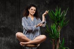 Mooi donkerbruin meisje die in tropische installaties over grijze achtergrond mediteren stock foto