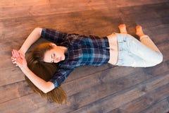 Mooi donkerbruin meisje in een blauw overhemd in een kooi en jeans met gaten die op de houten vloer liggen Het schot van de studi stock foto's