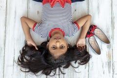 Mooi donkerbruin meisje met gestreepte kleding stock afbeelding