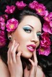 Mooi donkerbruin meisje met roze bloemen in haar Stock Foto