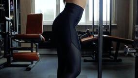 Mooi donkerbruin meisje in zwarte beenkappen en bovenkant die een opwarming in de gymnastiek doen Jong meisje het uitrekken zich  stock footage
