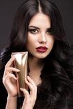 Mooi donkerbruin model: krullen, klassieke make-up en rode lippen met een fles van haarproducten Het schoonheidsgezicht Royalty-vrije Stock Afbeelding