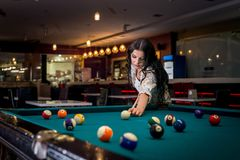 Mooi donkerbruine vrouwen speelbiljart in bar stock fotografie