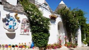 Mooi dorp van Alberobello met trullihuizen onder groene installaties en bloemen, hoofd toeristisch district, Apulia-gebied, South stock afbeelding