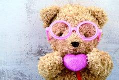 Mooi draag pop die roze glazen dragen en roze hartsha houden Royalty-vrije Stock Fotografie