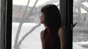 Mooi droevig meisje door het venster thuis stock videobeelden