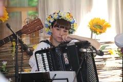 Mooi droevig, peinzend meisje in het nationale Oekraïense kostuum met harmonika Stock Foto's