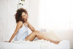 Mooi dromerig Afrikaans meisje die in nachtkleding met gesloten ogen thiking zitting op bed dromen Stock Foto's